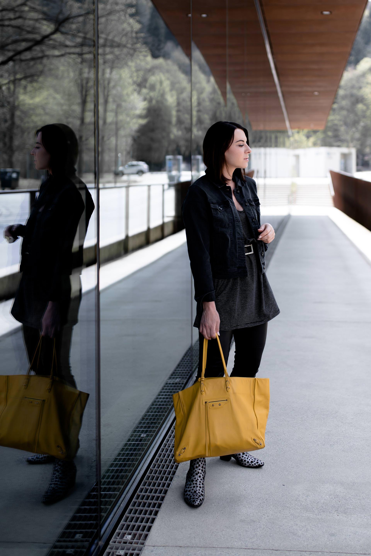 schwarze Lederhose kombinieren, dunkelgraue Jeansjacke stylen, T-Shirt-Kleid Outfit, Look mit Shirtkleid, gelbe Balenciaga Tasche, Frühlingsoutfit, Saint Laurent Boots, Modeblogger, www.whoismocca.com
